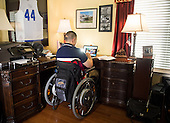 Afganistan war vet Josh Himan works on his computer at his family's home in Woodbridge, VA.