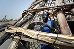 Deng Agany works on the framework of a thatched roof hut in Agok, a town in the contested Abyei region where tens of thousands of people fled in 2011 after an attack by soldiers and militias from the northern Republic of Sudan on most parts of Abyei. Although the 2005 Comprehensive Peace Agreement called for residents of Abyei--which sits on the border between Sudan and South Sudan--to hold a referendum on whether they wanted to align with the north or the newly independent South Sudan, the government in Khartoum and northern-backed Misseriya nomads, excluded from voting as they only live part of the year in Abyei, blocked the vote and attacked the majority Dinka Ngok population. The African Union has proposed a new peace plan, including a referendum to be held in October 2013, but it has been rejected by the Misseriya and Khartoum. The Catholic parish of Abyei, with support from Caritas South Sudan and other international church partners, has maintained its pastoral presence among the displaced and assisted them with food, shelter, and other relief supplies.