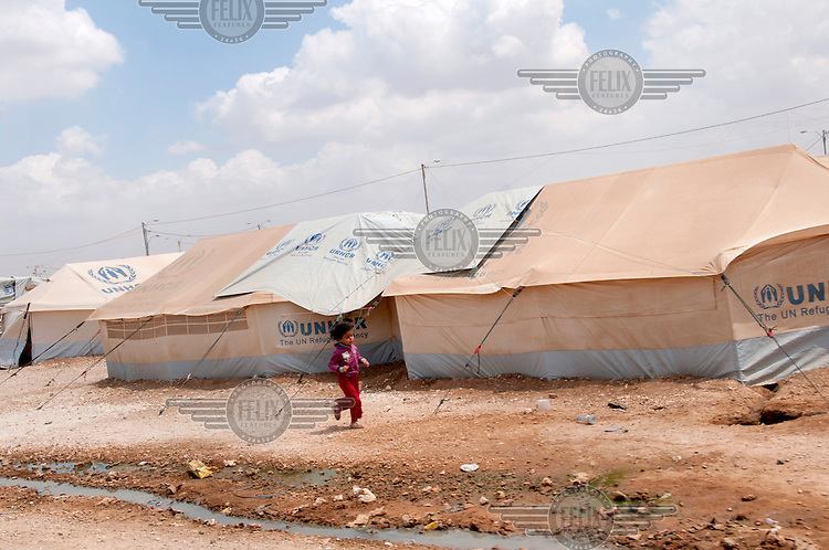 A girl runs past tents set up by UNHCR in the Zaatari refugee camp for Syrian refugees in Jordan. /Felix Features
