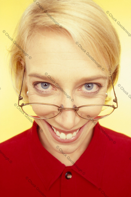 Stock Image of a blond sexy secretary in a red shirt weariing glasses and a big-eyed smile.