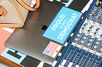 """A laptop with a sticker reading """"Proud to be a Democrat"""" and an American flag with QR Code as stars lays next to the soundboard after candidate Senator Cory Booker (D-NJ) spoke at a house party at the home of State Senator Shannon Chandley and Tom Silva in Amherst, New Hampshire, USA, on Sat., Apr. 6, 2019."""