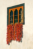 Red chili peppers hung from a residential window to dry in the sun. Pepers drying on roof tops, from windows or on canvas on the ground is symbolic of this country. Photographed in Thimpu, capital of Bhutan.