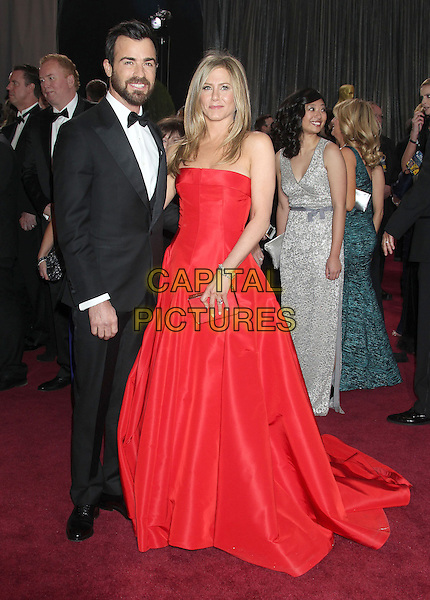 Justin Theroux & Jennifer Aniston (wearing Valentino).85th Annual Academy Awards held at the Dolby Theatre at Hollywood & Highland Center, Hollywood, California, USA..February 24th, 2013.oscars full length black tuxedo white shirt bow tie beard facial hair red strapless dress gown couple engaged gold clutch bag .CAP/ADM/RE.©Russ Elliot/AdMedia/Capital Pictures.