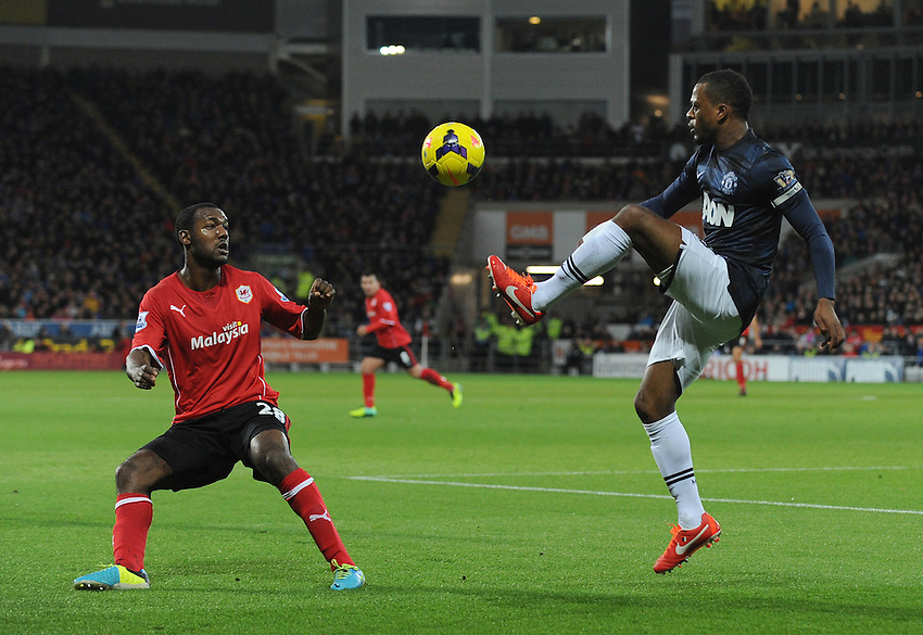 Manchester United's Patrice Evra clears from the chasing Cardiff City's Kevin Theophile-Catherine<br /> <br /> Photo by Ian Cook/CameraSport<br /> <br /> Football - Barclays Premiership - Cardiff City v Manchester United - Sunday 24th November 2013 - Cardiff City Stadium - Cardiff<br /> <br /> &copy; CameraSport - 43 Linden Ave. Countesthorpe. Leicester. England. LE8 5PG - Tel: +44 (0) 116 277 4147 - admin@camerasport.com - www.camerasport.com