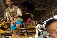 A child injures his arm while playing on earth moving equipment at displaced person's camp near Baan Nam Khem, Thailand. Many of the children in the camp are orphans, having lost entire families in the Asian Tsunami. January 7, 2005. (James J. Lee for USA Today)