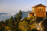 A wooden chalet perched on the summit of a fir-clad mountain enjoys panoramic views of the surrounding peaks