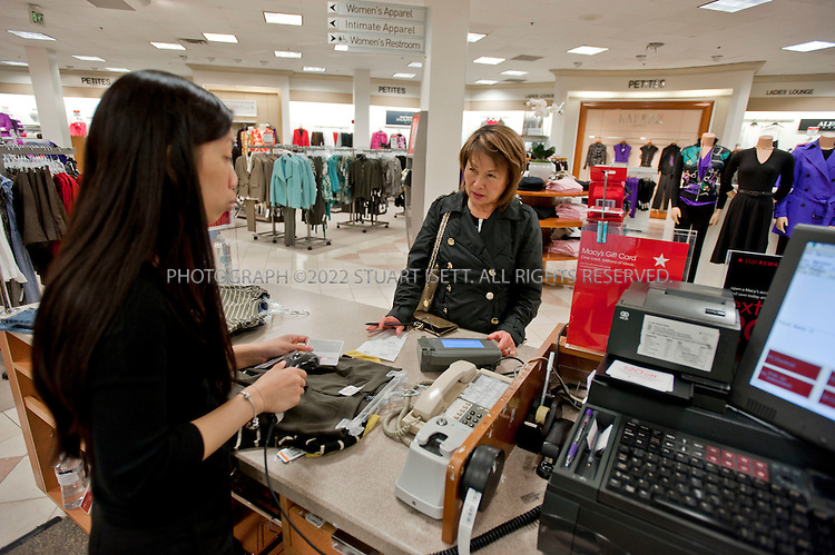 """9/23/2010--Seattle, WA, USA..Here: Sachiko Conner, 62 (right), of Bellevue WA, buys clothes at the large 'petites' section of the Macy's store at Bellevue Square, in Bellevue, WASH. She is helped by Macy's employee, Sally Pot, 30. ...Macy's in Bellevue,  WASH., near Seattle. After years of acquiring other department stores and trying to make them all look the same, retailers like Macy's and Saks are now trying to make each store seem local and authentic. The Seattle store, in Bellevue Square, has an Asian and Indian population, lots of corporate types and """"Microsoft wives,"""" as the store manager referred to them...©2010 Stuart Isett. All rights reserved."""