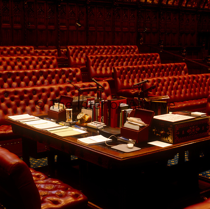 The Clerk's Table at the centre of the Chamber, on which can be seen the division hour glass, for timing votes, and a  gold embossed despatch box