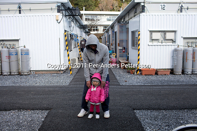 RIKUZENTAKATA, JAPAN - DECEMBER 4: A father plays with his daughter at a temporary housing complex on December 4, 2011, in Rikuzentakata, Japan. Northeastern Japan's coastline was struck by an earthquake measuring 9.0 on the Richter scale and a Tsunami on March 11, 2011 which destroyed villages and livelihoods for hundreds of thousands of people. Almost 16,000 dead, thousands missing, more than 700,000 properties destroyed and an estimated 387,000 survivors lost their homes. Its estimated that it will take more than five years to rebuild. The cost is estimated to 309 billion U.S. dollars, the world's most expensive natural disaster. Many children suffered especially with school destroyed, education interrupted and the loss of family members took a heavy toll. (Photo by Per-Anders Pettersson)