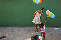 RIO DE JANEIRO, BRAZIL - FEBRUARY 23, 2014: A girl plays with balloons<br />  during the annual T&aacute; Pirando, Pirado, Pirou! carnival street parade on February 23, 2014 in Rio De Janeiro, Brazil. It looks like any of the other 450 or so street parties, locally called &ldquo;carnival blocks,&rdquo; that parade through Rio de Janeiro during the raucous pre-Lenten festivities that draw hundreds of thousands to the city each year. What makes this party different are its performers and organizers: psychiatric patients and their doctors, therapists, family members, neighbors and passers-by. The group, called T&aacute; Pirando, Pirado, Pirou!, which roughly translates as &ldquo;We&rsquo;re freaking out, we already freaked out!&rdquo;, began ten years ago when Brazil was in the process of dismantling its century-old system of mental asylums. A law passed in 2001 called for long-term outpatient psychiatric care to be offered primarily in community clinics. The number of such clinics increased more than fivefold in the following decade, while the number of asylum beds for psychiatric patients dropped 40 percent nationwide.<br /> <br /> Daniel Berehulak for The New York Times