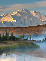 Morning fog over the calm waters of Wonder Lake at sunrise, Denali looms in the distance, Denali National Park, Alaska.