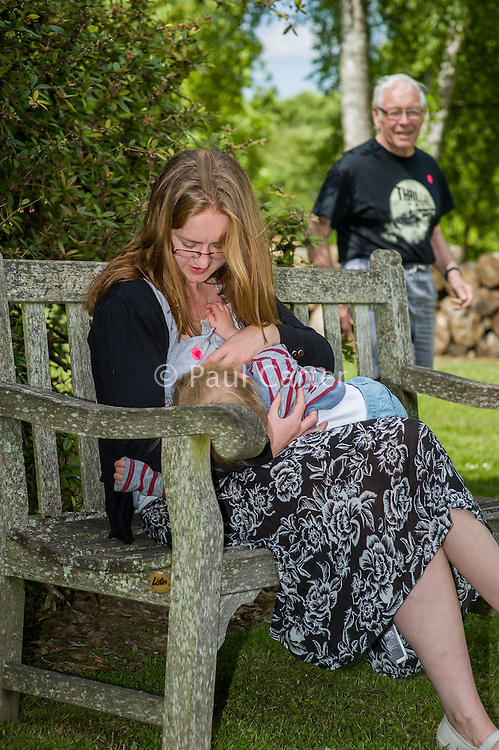 A mother  breastfeeding her child during a family outing to a local park and gardens, with a passer-by in the background.<br /> <br /> 11-06-2015<br /> Hampshire, England, UK<br /> <br /> © Paul Carter / wdiip.co.uk