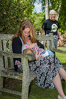 A mother  breastfeeding her child during a family outing to a local park and gardens, with a passer-by in the background.<br /> <br /> 11-06-2015
