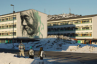 Nuuk, Greenland - A mother and kids walk past a public housing estate in Nuuk, Greenland, March 2016. Nuuk is the capital and largest city of Greenland. It is the seat of government and the country's largest cultural and economic centre. The major cities closest to the capital are Iqaluit and St. John's in Canada and Reykjavík in Iceland. Nuuk contains almost a quarter of Greenland's population, and also has the tallest building in Greenland. Nuuk is the seat of government for the Sermersooq municipality. In January 2016, it had a population of 17,316.