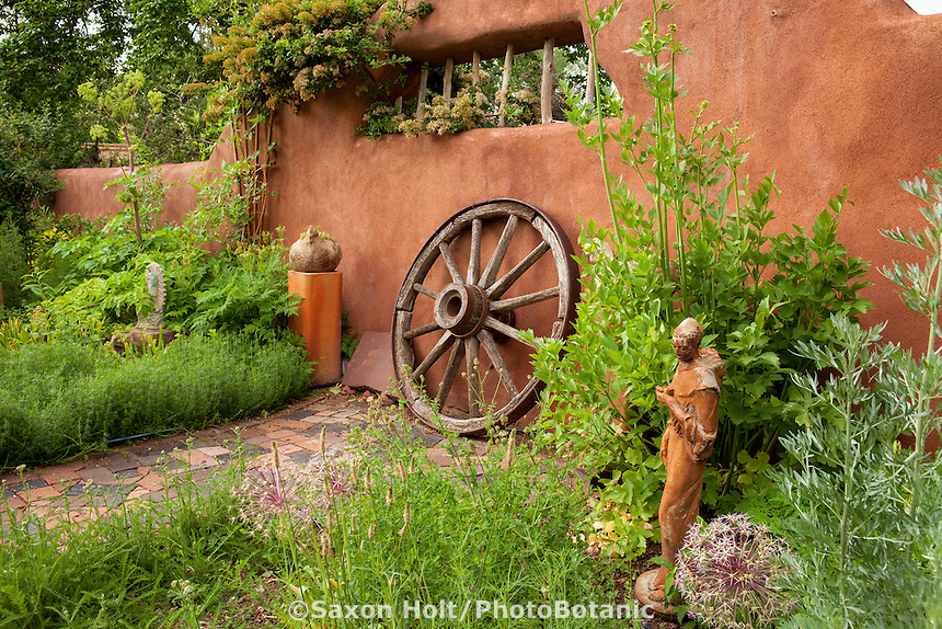 New Mexico herb garden with rustic wagon wheel against stucco wall; Elspeth Bobbs Garden