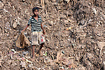 A boy scavenges in the municipal garbage dump in Chennai, India. He and other boys who work in the dump spend their nights safely in a shelter sponsored by the Madras Christian Council of Social Service.