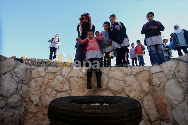 A Palestinian man helps students to through a sewage tunnel to get to school near the West Bank village of Jaba' , southern Jinin, on Feb. 05, 2013. Students try to avoid cross the main road traffic which caused many accidents and killed students. Photo by Issam Rimawi