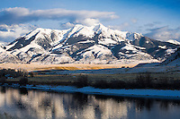 The sun sets over a snow draped Emigrant Peak and the Yellowstone River in Paradise Valley, Montana.