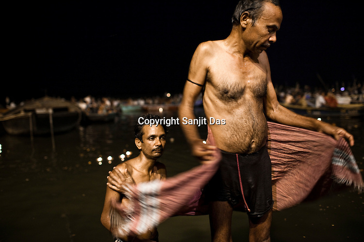A man gets dries himself after taking a holy dip in the ganges at the Dashashwamedh Ghat in the ancient city of Varanasi in Uttar Pradesh, India. Photograph: Sanjit Das/Panos