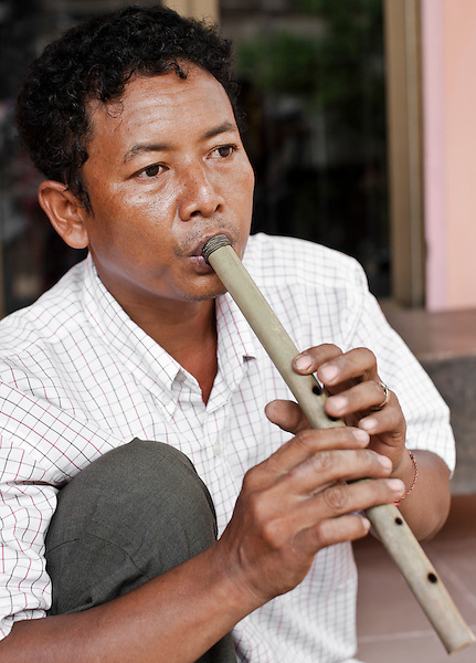 Wind instrument maker Yim Seih Chot plays a Kloy at his home outside Phnom Penh, Cambodia. ..The Kloy, (Cambodian flute) is said to have originated from around the seventh century. Records of its existence have been found in carvings on ancient stone pillars, dating from around the year 611 AD....Cambodian Living Arts works to support the revival of traditional Khmer performing arts and to inspire contemporary artistic expression. CLA supports arts education, mentorship, networking opportunities, education, career development, and income generating projects for master performing artists who survived the Khmer Rouge as well as the next generation of student artists....