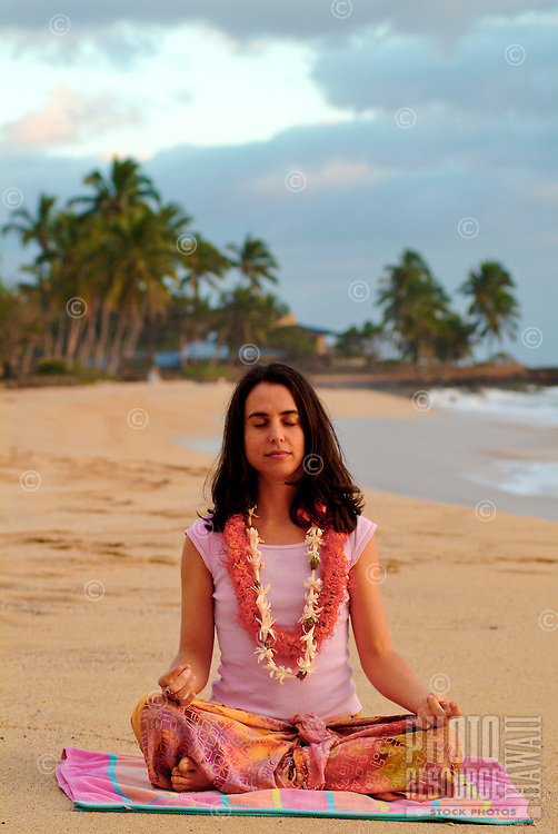 Woman age 32 sitting in lotus position meditating with flower leis on at Mahaka beach, Leeward Oahu