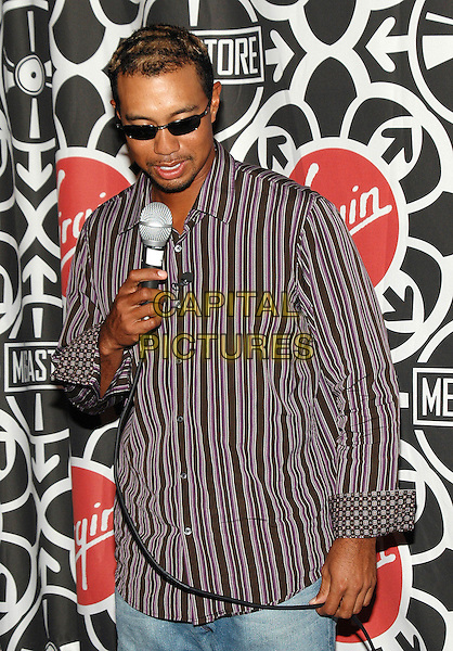 "TIGER WOODS.Appearance at the Virgin Megastore in Times Square to promote his new Electronics Arts game, ""Tiger Woods:PGA Tour 2006"", New York, New York..September 26th, 2005.Photo Credit: Patti Ouderkirk/AdMedia/Capital Pictures.Ref: PO.half length striped shirt microphone sunglasses shades.www.capitalpictures.com.sales@capitalpictures.com.© Capital Pictures."
