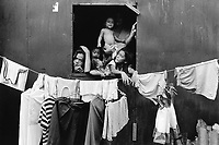 Philippines. National Capital Region. Manila. Paradise village. A father and his five children stand in their wooden hut and look through the window. A laundry with clean clothes is hanging on a rope and drying in the sun. Paradise village has a population of 15'000 people and is a part of Barangay Tonsuya situated on Lettre Road in Malabon. Manila is part of the National Capital Region (NCR) on Luzon island. Manila is the capital of the Philippines and one of the sixteen cities that comprise Metro Manila. Metro Manila is the most populous metropolitan area in the Philippines. © 1999 Didier Ruef