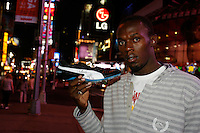 Usain Bolt  with the World Record spikes in Times Square, NYC hours after setting a World Record in the 100m dash with a time of 7.72sec. at the Reebok Grand Prix Meet held at ICAHN Stadium on Saturday, May 31, 2008. Photo by Errol Anderson, The Sporting Image.