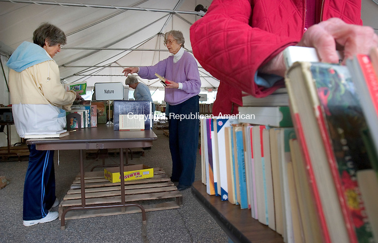 SOUTHBURY, CT. 15 May 2008-051508SV06--From left, Marti Swift and Ann Laeuchli set up for the ibrary book sale as Dorothy Guntner arranges books at Heratage Village in Southbury Thursday. The Heritage Village Library volunteers were setting up for the library's annual book sale to be held Friday, Saturday and Sunday in Heritage Village. The book sale is from 9:30 a.m. to 5 p.m. Friday May 16 and Saturday May 17, and from 10 to 3:30 p.m. Sunday May 18. There will be a wide choice of hardcover and paperback books, puzzles, CDs, DVDs, records and cassette tapes.<br /> Steven Valenti Republican-American