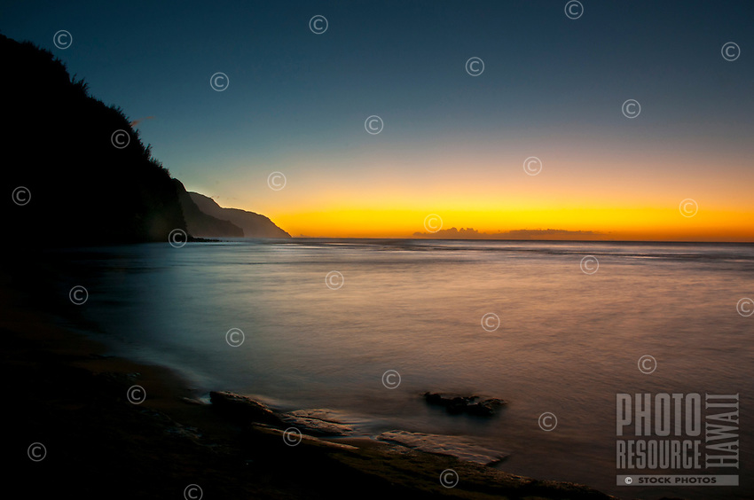 The setting sun casting a golden hue across the sky, touching the cliffs of Na Pali and the ocean off Ke'e Beach, Kauai.