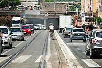 Un ciclista percorre un tratto di strada sprovvista di pista ciclabile e ad alta densità di traffico