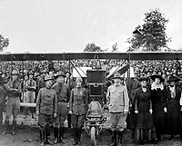 Ruth Law, the only woman permitted to wear the government aviation uniform in France for nonmilitary purposes, with members of the 29th Division, Camp McClellan, AL, ca.  1918.  (National Archives Gift Collection)<br />