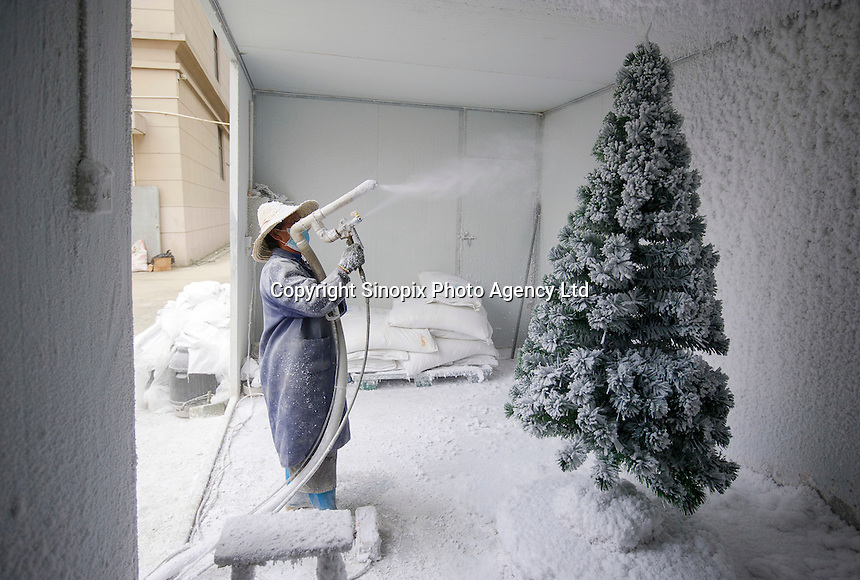 November 28, 2015, Yiwu China - A worker sprays a Christmas tree with artificial snow.  At Sinte An Christmas tree factory. Sinte An produces a variety of artificial trees for global export throughout the year.Photo by Dave Tacon / Sinopix
