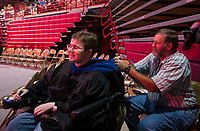 NWA Democrat-Gazette/BEN GOFF @NWABENGOFF<br /> Hal Walter helps his son Raymond Walter with his hood and gown Saturday, May 11, 2019, before the University of Arkansas all university commencement ceremony in Bud Walton Arena in Fayetteville. Raymond Walter graduated with a Ph. D. in physics.