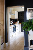 The kitchen viewed from the entrance hall; a colour scheme of grey and black throughout the house co-ordinates all the living spaces