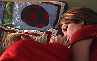 Heather Jacobs clasps hands in bedtime prayer with her son, Justin, 10.   Bedtime is cherished by Heather, as it is about the only time in the day where she will get one-on-one time with each of her children. Heather lost her husband, Eric, in a plane crash in 2006 when she was eight months pregnant with their youngest, Ella, and has since been raising her five young children on her own.