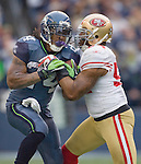 Seattle Seahawks running back Marshawn Lynch is tackled by San Francisco 49ers linebacker Larry Grant  at  CenturyLink Field in Seattle, Washington on December 24, 2011. The 49ers came from behind to beat the Seahawks 19-17. ©2011 Jim Bryant Photo. All Rights Reserved.