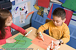 Educaton preschool 4-5 year olds art activity boy and girl sitting at table drawing with markers using opposite hands right hand left hand horizontal boy wearing watch