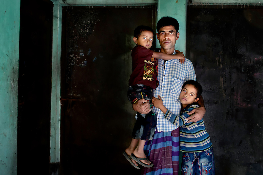 Shaheb Ali, holds his sons Siam, 7, right, and Saif, 5, left, posing for a portrait in front of the living room in which his wife Shirin Akhter (24) was killed when a factory fire ravaged Tazreen Fashions, in Ashulia, Bangladesh.