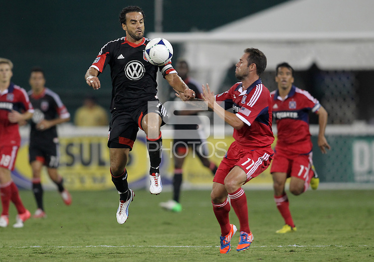 WASHINGTON, DC. - AUGUST 22, 2012:  Dwayne DeRosario (7) of DC United jumps for the ball in front of  Daniel Paladini (11) of the Chicago Fire during an MLS match at RFK Stadium, in Washington DC,  on August 22. United won 4-2.
