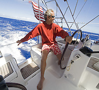 Man at the helm of an American sailboat at speed in the trade winds, during a Pacific crossing