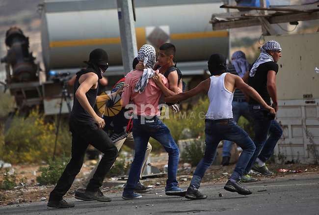 Palestinian protesters carry an injured comrade during clashes with Israeli security forces near the Jewish settlement of Bet El, near the West Bank city of Ramallah, on October 13, 2015. A wave of stabbings that hit Israel, Jerusalem and the West Bank this month along with violent protests in annexed east Jerusalem and the occupied West Bank, has led to warnings that a full-scale Palestinian uprising, or third intifada, could erupt. The unrest has also spread to the Gaza Strip, with clashes along the border in recent days leaving nine Palestinians dead from Israeli fire. Photo by Shadi Hatem
