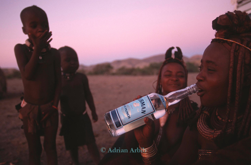 A  Himba girl drinks a rum punch drink...Alcoholism is becoming an increasing problem within the Himba region.   A Himba  village, Northern Namibia.