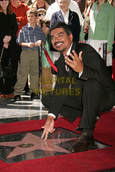 GEORGE LOPEZ.George Lopez Star on The Hollywood Walk Of Fame, Hollywood, California, USA..March 29th, 2006.Photo: Russ Elliot/AdMedia/Capital Pictures.Ref: RE/ADM.full length kneeling black suit.www.capitalpictures.com.sales@capitalpictures.com.© Capital Pictures.