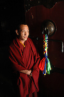 A monk stands in the doorway of the Mindroling Monastery in Tibet. The Mindroling Monastery is the oldest Nyingmapa monastery (Nyingmapa is the earliest order of Tibetan Buddhism) and received significant damage during the Cultural Revolution.