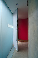 The concrete entrance hall benefits from a wall of opaque glass and an interior wall painted a bright red