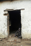 A Dinka child in a doorway at Thiet feeding camp in Southern Sudan. Hundreds of Dinka tribes people having had their villages bombed and burnt  by the Khartoum forces  have travelled hundreds of miles to avoid  starvation a the feeding centre.