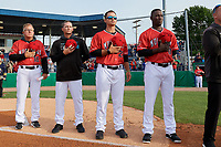 Batavia Muckdogs coaches Tom Lawless, Chad Rhoades, Nathan Mikolas, and Rigoberto Silverio (L-R) during the national anthem before a NY-Penn League game against the Auburn Doubledays on June 14, 2019 at Dwyer Stadium in Batavia, New York.  Batavia defeated 2-0.  (Mike Janes/Four Seam Images)