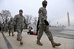 "Members of the military walk past the Washington monument at the ""We Are One"" concert in celebration of Barack Obama's inauguration as president of the United States at the Lincoln Memorial in Washington, DC on January 18, 2009."