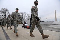 """Members of the military walk past the Washington monument at the """"We Are One"""" concert in celebration of Barack Obama's inauguration as president of the United States at the Lincoln Memorial in Washington, DC on January 18, 2009."""